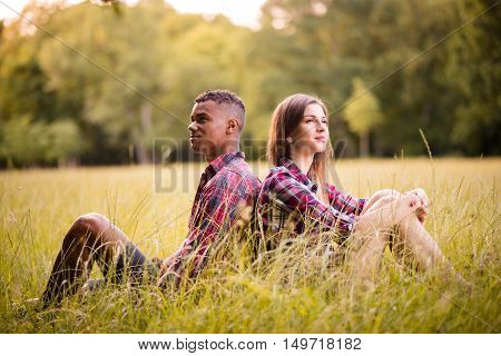Young multi racial couple sitting in grass and leaning with their backs - outdoor in evening nature
