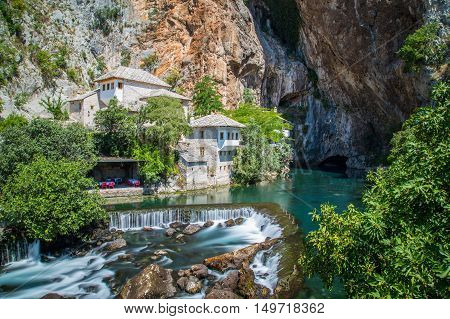 A waterfall at Blagaj in Bosnia and Herzegovina. Buildings can be seen. poster