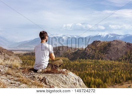 Man meditating on the Altay mountains background