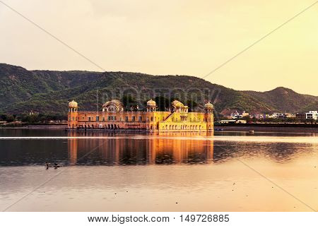 Jal Mahal palace at sunset in Jaipur, India. Popular landmark surrounded by water. Mountains at the background