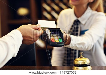 Midsection of man at counter paying for hotel