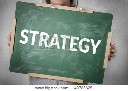 Strategy text written on chalkboard. Business or education concept.