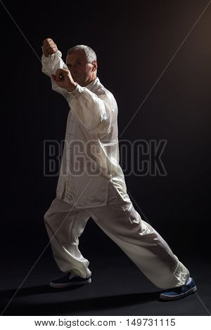 Senior man enjoys exercise Tai Chi indoor.