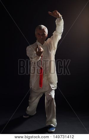 Senior man enjoys practicing Tai Chi with sword indoor.