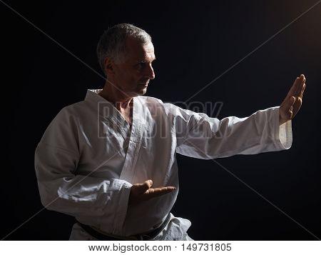 Photo of senior man enjoys practicing karate indoor.