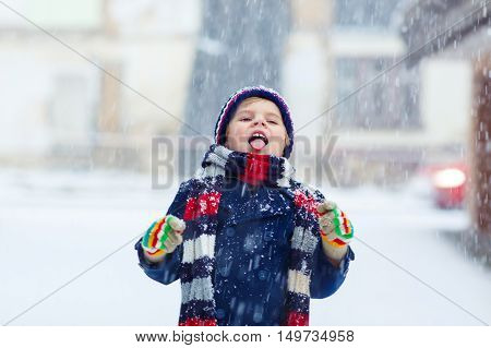 Winter portrait of kid boy in colorful clothes, outdoors during snowfall. Active outoors leisure with children in winter on cold snowy days. Happy child having fun with snow