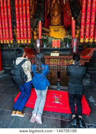 Shanghai China - October 26 2013: Chinese believers praying in the Jade Buddha Temple in Shanghai China. Buddhism is enjoying a revival in modern liberal China.