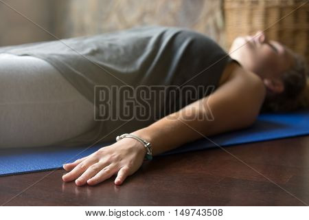 Attractive young woman working out at home, doing yoga exercise on blue mat, lying in Shavasana Corpse or Dead Body Posture , resting after practice, meditating, breathing. Close-up, focus on hand