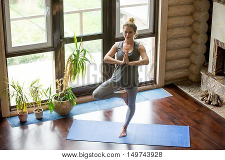 Full length portrait of attractive young woman working out at home in living room, doing yoga or pilates exercise on blue mat, standing in Vrksasana Posture, Tree Pose