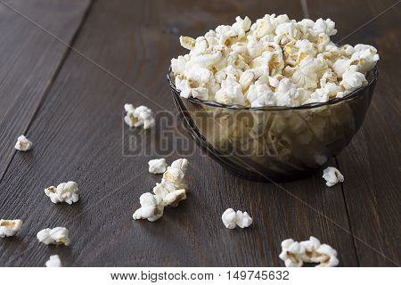 Salty popcorn on the wooden table. Bowl of popcorn with cheese flavor.