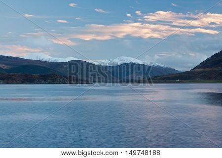 Snowcapped mountains by the sea at Ullapool Scotland