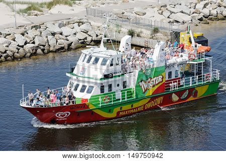 KOLOBRZEG POLAND - JUNE 22 2016: Fishing boat named Monika III enters in the port on board are visible people returning from a tourist cruise on the waters of the Baltic Sea
