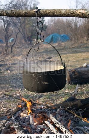 Kettle with food above the fire in the camping poster