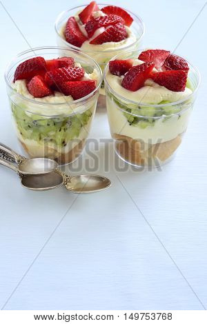 Layered dessert with strawberries kiwi biscuit and cream, Trifle, vertical