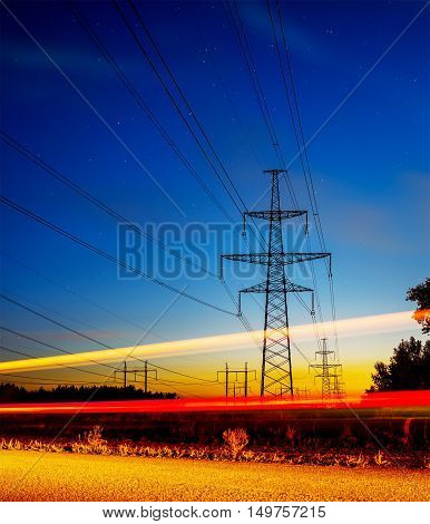 Pylons and electricity powerlines at night with traffic lights in front