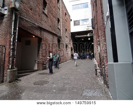 SEATTLE- JUNE 24 : People look at the The Market Theater Gum Wall in downtown Seattle on June 24 2016. It is a local landmark in downtown Seattle in Post Alley under Pike Place Market.