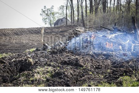 horizontal image of a pile of field stubble smoldering with a lot of smoke and small flames burning.