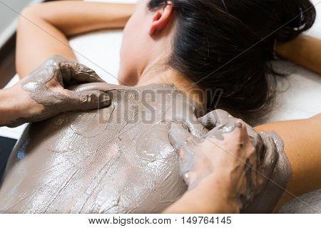 Beautiful Young Woman Having Clay Body Mask Apply By Beautician. Detox Ritual.