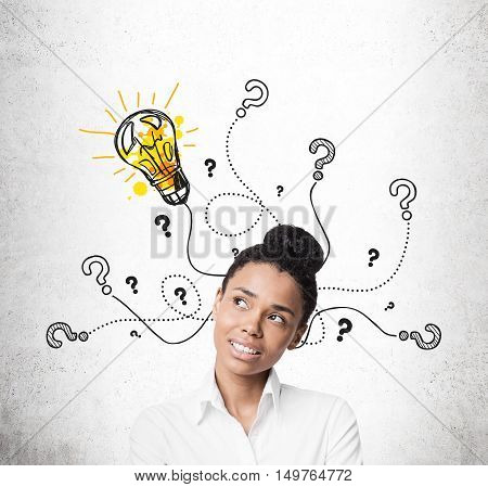 Close up of African American girl thinking. Light bulb and question mark sketches are on concrete wall behind her. Concept of solution finding.