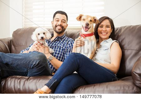 Portrait of a cute young Hispanic couple relaxing at home and sitting with their dogs and smiling