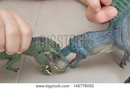 kid playing tyrannosaurus and spinosaurus toys on a sofa at home