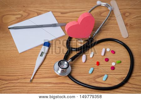 Stethoscope and tablets, heart in the middle, prescription, tablet pen, and thermometer photo for heart disease. Dr  appointment poster