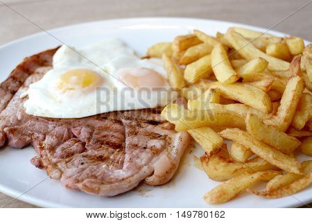 Gammon steak double eggs and chips served on a white plate