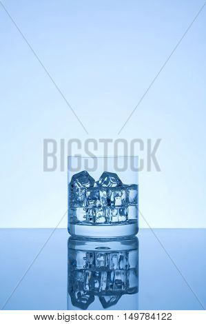Glass with ice cubes blue color tone