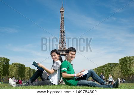 Asian couple student reading book together at outdoors park near Eiffel Tower in Paris France. Abroad study in Paris France.