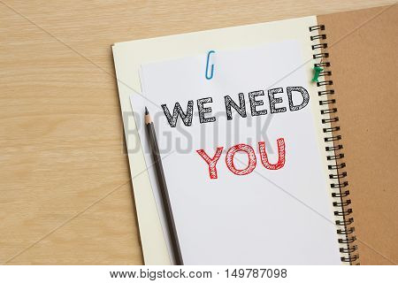 Text we need you on white paper and pencil / business concept