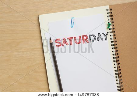 Saturday text on white paper and pencil, book on wood desk / Saturday concept / top view