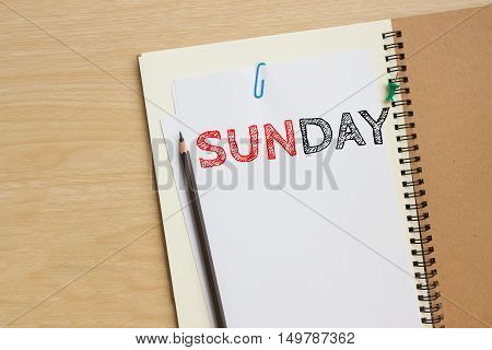 Sunday text on white paper and pencil, book on wood desk / tuesday concept / top view