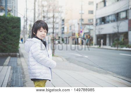 Cute Asian child walking in the city streetOsaka Japn