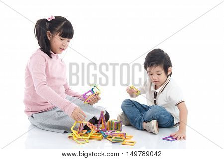 Cute Asian children playing with lots of colorful magnet plastic blocks kit on white background isolated