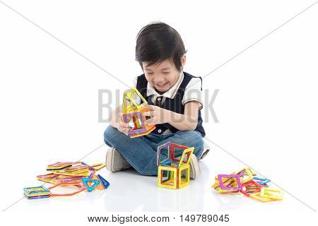 Cute Asian child playing with lots of colorful magnet plastic blocks kit on white background isolated