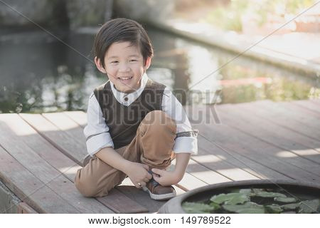 little asian child tying his shoes outdoorsvintage filter