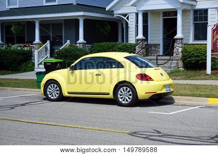 HARBOR SPRINGS, MICHIGAN / UNITED STATES - AUGUST 1, 2016: A yellow Volkswagen Beetle is parked on Third Street near downtown Harbor Springs.