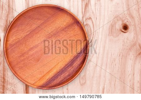 empty wood plate on wood table background / can be used display your product / Top view.