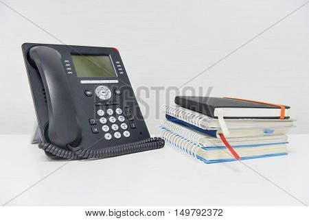 Black IP Phone and stack of books on the white table