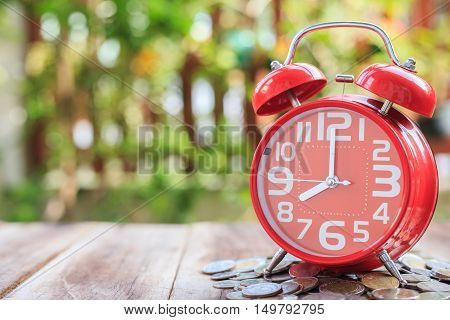 Red Alarm Clock And Pile Of Coins On Wooden Plank