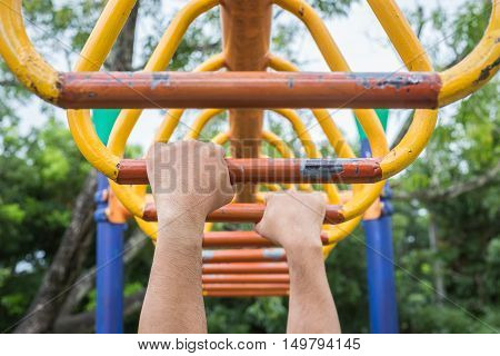 Hand Hanging On Steel Bar For Trapeze. Outdoor Exercise Equipment At Public Park