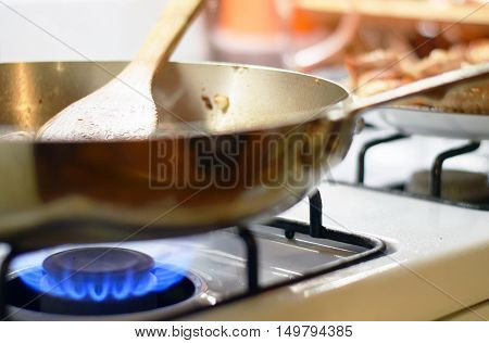 Wooden spatula stirring food in saute pan