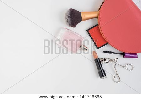 Top view of pink cosmetic bag and make up products - powder brush perfume brush on lipstick mascara and eyelash curler on white background