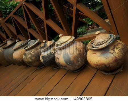 Ancient water clay pottery. Water pot on the shelf for guests. Thailand culture, water pottery for guests