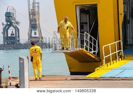 Piombino Italy - June 30 2015: Workers prepare a gangway for the exit of passengers in the seaport