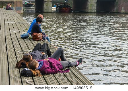 Amsterdam the Netherlands - October 03 2015: People resting at berth near the water