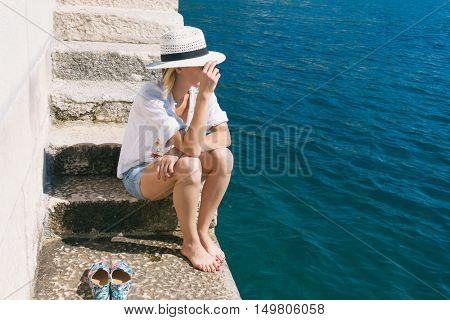 Young traveler woman resting at harbor by the sea. Vacation concept.