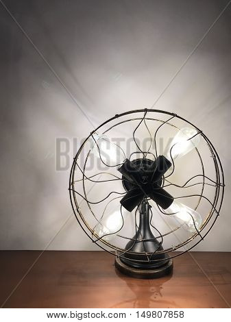 Antique looking table lamp fan in lighted up in a dark room