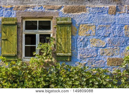 Traditional german house window and stone wall - Architecture background from a medieval german house with its blueish wall the wooden window and the vines