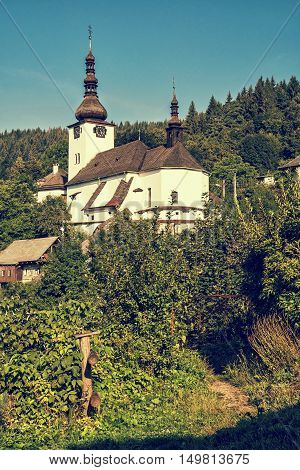 Fortified church in Spania Dolina Slovak republic. Travel destination. Blue photo filter. Religious architecture. Beautiful place. Vertical composition.